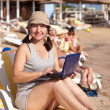 Mature womwith laptop at resort beach — Stock Photo #13676592