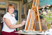 Female artist paints anything on canvas — Stock Photo