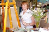 Kobieta artysta maluje obraz — Zdjęcie stockowe