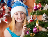 Girl in christmas hat near spruce — Stock Photo