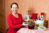 Mature woman brews herbs — Stock Photo