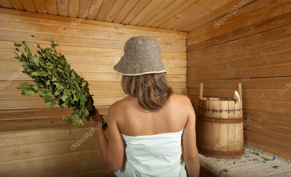Girl is steamed in the sauna with birch twigs  Stock Photo #13675399