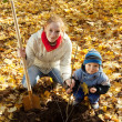 Stock Photo: Womwith son setting tree in autumn