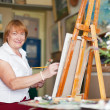 Female artist paints anything on canvas - Stock Photo