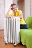 Mulher sorridente perto do radiador quente — Fotografia Stock