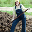 Farmer works with animal manure - Stock Photo