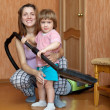 Family with vacuum cleaner — Stock Photo