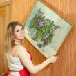 Woman  hangs the art picture on wall - Stock Photo