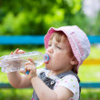 Two-year child drinks from plastic bottle — Stock Photo #15260583