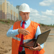 Builder works at construction site - Stock Photo