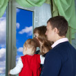 Stock Photo: Family looking out window