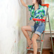 Girl paints wall with brush - Zdjęcie stockowe