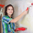 Woman paints wall with roller - Zdjęcie stockowe