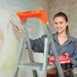 Woman paints wall with brush - Zdjęcie stockowe