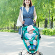 Womwalking with baby stroller — Stock Photo #15262327