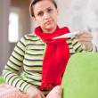 Sick woman on sofa with thermometer — Stock Photo
