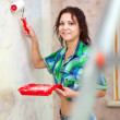 Happy woman paints wall with roller - Stock fotografie