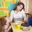 Mother feeding baby and  using  latop - Stock Photo
