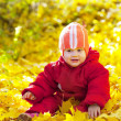 Year-old child sitting on maple leaves — Stock Photo