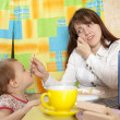 Businesswoman feeding baby and  speak by mobile - Stock Photo