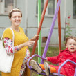 Pregnant woman with child on swing in autumn park — Stock Photo