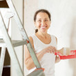 Happy mature woman paints wall — Stok fotoğraf