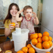 Stock Photo: Mother and daughter making orange juice