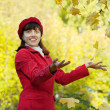 Stock Photo: Girl throwing yellow maple leaves