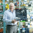 Royalty-Free Stock Photo: man holds  automotive   tool set in  auto parts store