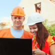 Two happy builders in hardhat - Stock Photo