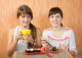 Vrouwen eten sushi rollssuşi rulo yiyen kadınlar — Stok fotoğraf