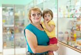 Woman with child chooses drugs at pharmacy — Stock Photo
