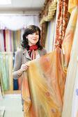 Woman chooses draperies — Stock Photo