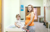 Pregnant woman with child waits to attendance of doctor — Stock Photo
