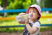 Child drinks from plastic bottle — Stock Photo