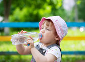 Two-year child drinks from plastic bottle — Stock Photo