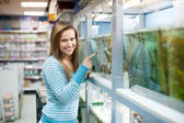 Woman chooses fish at petshop — Stock Photo