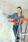 Happy girl paints wall with brush — Stock Photo