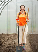 Happy woman with tools in hothouse — Stock Photo