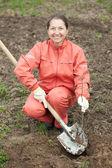 Kvinna återställa groddar i orchard — Stockfoto