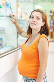 Pregnant woman at the pharmacy drugstore — Stock Photo