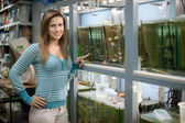 Woman chooses fish in aquariums — Stockfoto