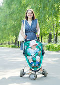 Woman walking with baby stroller — Stock Photo