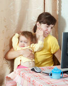 Woman with crying baby working with computer — Stock Photo