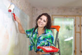 Woman paints wall at home — Stock Photo