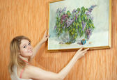 Woman hangs the picture on wall at home — Stock Photo