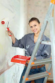 Woman paints wall at home — Stok fotoğraf