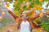 Happy woman throws leaves — Stock Photo