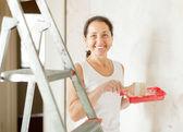 Happy mature woman paints wall — Foto de Stock