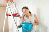 Weariness woman makes repairs at home — Stock Photo